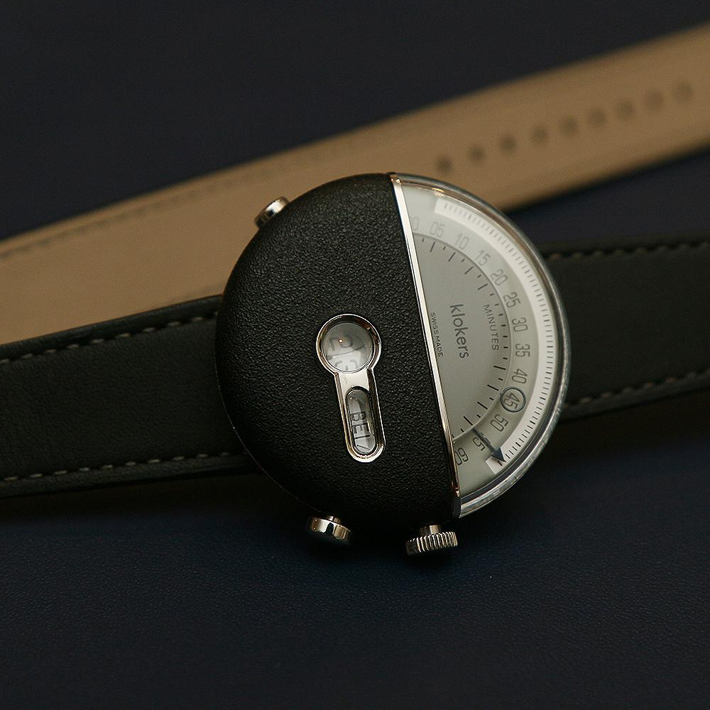 Klok-02將面盤一分為二,上方是逆跳分針與秒針,下方的視窗則是小時顯示與時區城市縮寫。(Klok-02配雙圈錶帶,定價NT$37,100)