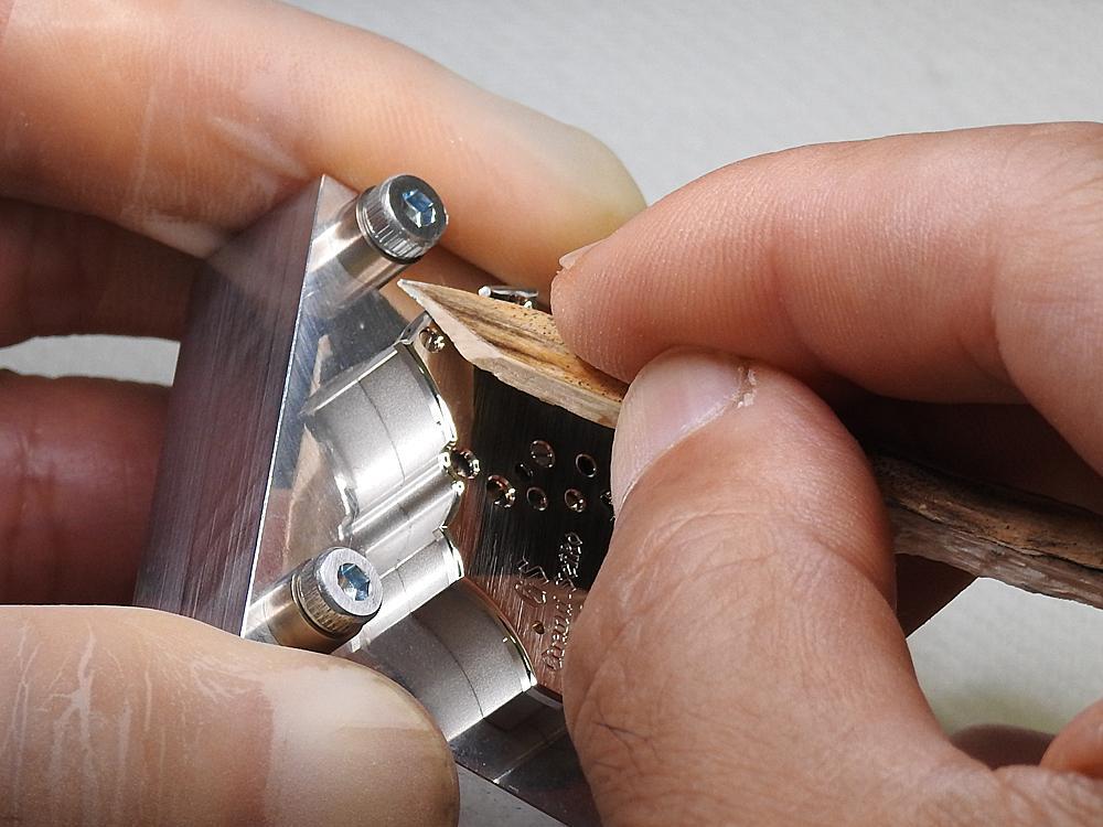 手持木條替9R01八日鍊Spring Drive機芯打磨倒角的「微型藝術大師工房」製錶師。雜時計研發部門「微型藝術大師工房」則是SEIKO的複雜腕錶研發中心,也是SEIKO最優秀製錶職人的聚集之地。