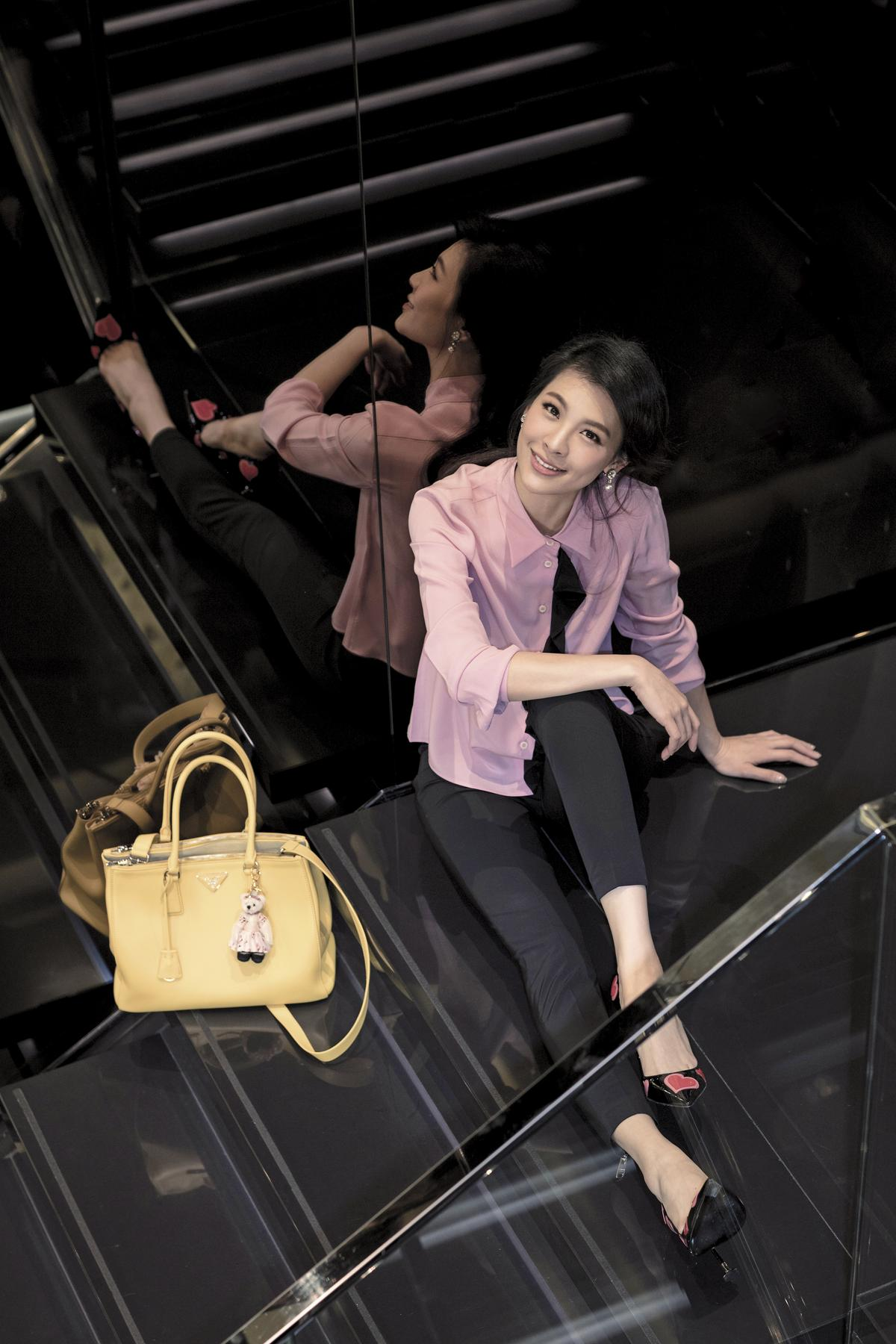粉色絲質襯衫,NT$27,000。黑色西裝褲,NT$20,000。Safano黃色手提包,NT$74,000。小熊吊飾,NT$10,000。愛心圖騰高跟鞋,NT$35,500(All by PRADA)