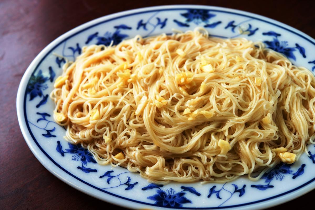 以雞湯、蒜頭及豬油快速拌過的「麻油麵線」,上桌時伴有較多湯水,趁熱吃來彈Q滑口。(100元/大份)