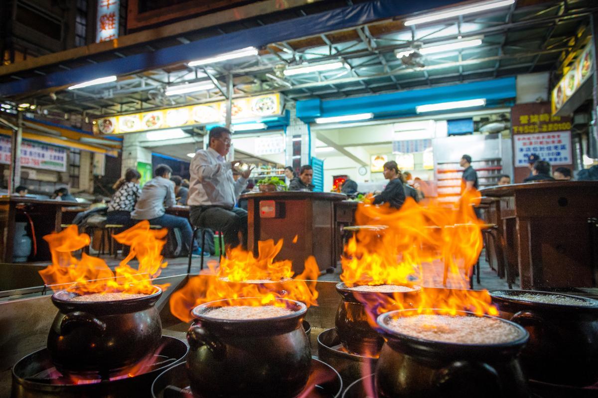 裝盛著羊肉爐的深色九母甕,正燃燒著酒精,藍青色火焰持續20~30秒,現場氣味濃郁、場景生猛,客人都願意坐在戶外一邊捱著冷、喝著熱湯,一邊欣賞暗夜火焰秀。