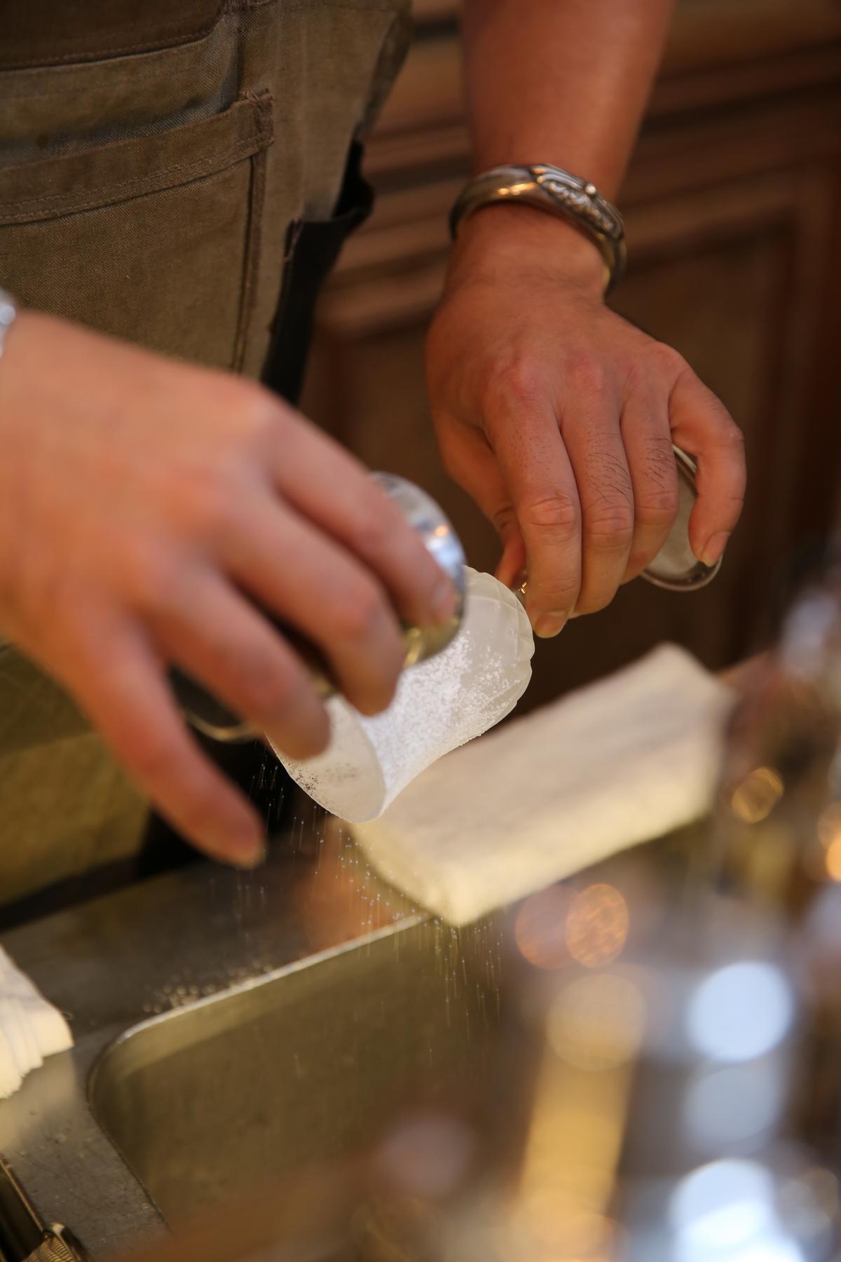小T仔細地在杯身撒上糖粉。