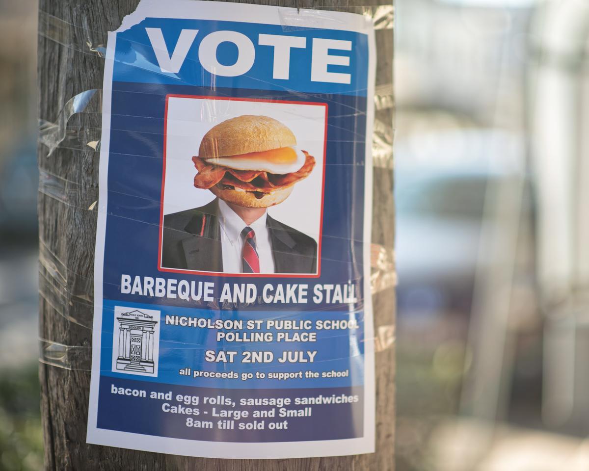 2016年7月2日澳洲聯邦選舉,海報上明白標示投票所外攤位供應培根蛋捲、香腸三明治等各類食物,所有收入捐給當地學校。(取自東方IC)
