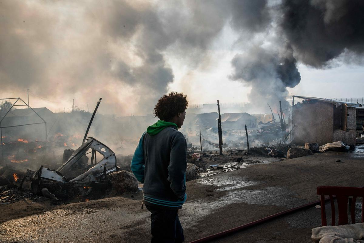 October 26, 2016 - Calais, France - Chaotic scenes of the jungle as the camp is evacuated, because of the danger from all the fires in Calais, 2016年10月26日,被稱為「叢林」的法國加萊難民營發生大火的現場混亂場面。基於安全因素法國當局封鎖了難民營的入口。(取自東方IC)