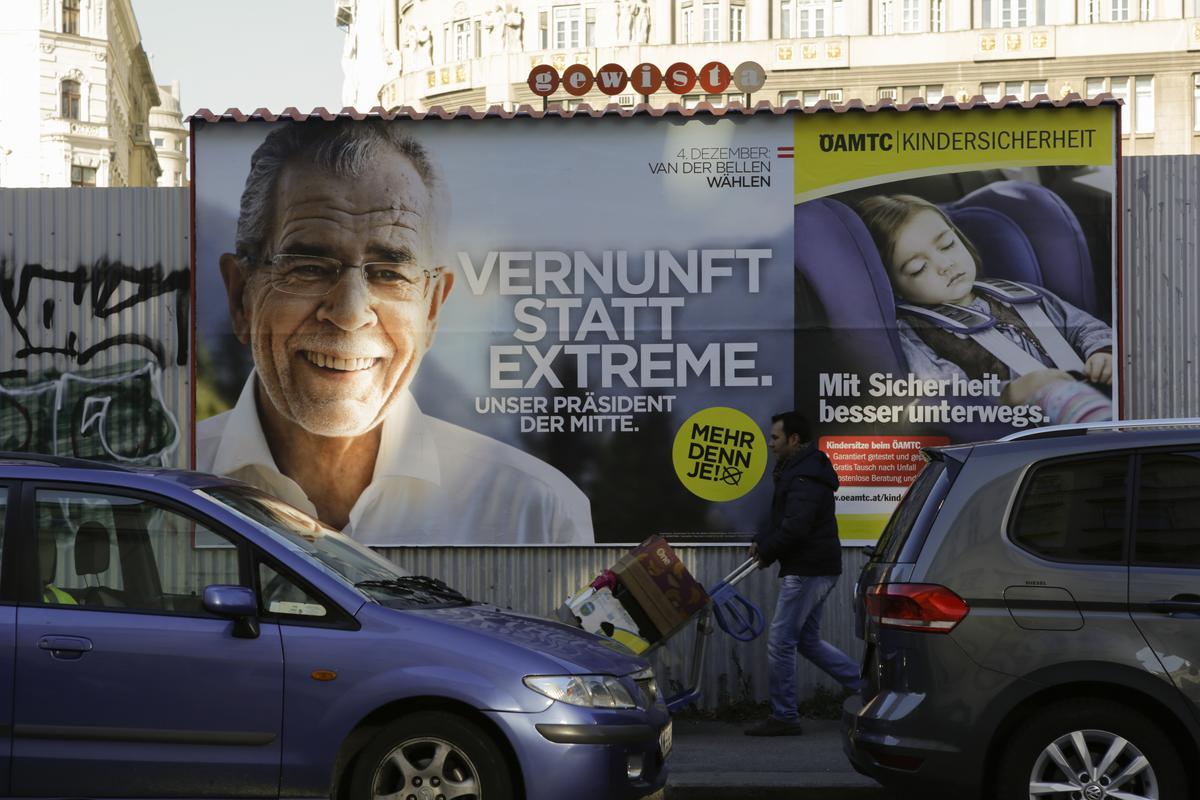2016年12月3日,一名民眾行經奧地利綠黨總統候選人范德貝倫的競選海報。冗長、紛亂、充滿激情的選戰盤據奧地利一整年的政治新聞版面。(取自東方IC)