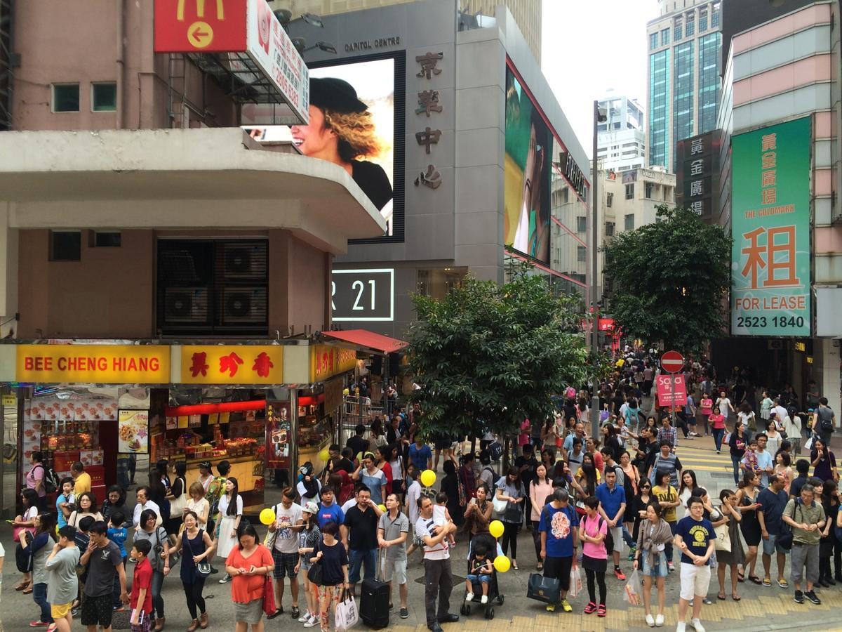 壅擠的人潮穿梭在招牌密掛的香港街巷。