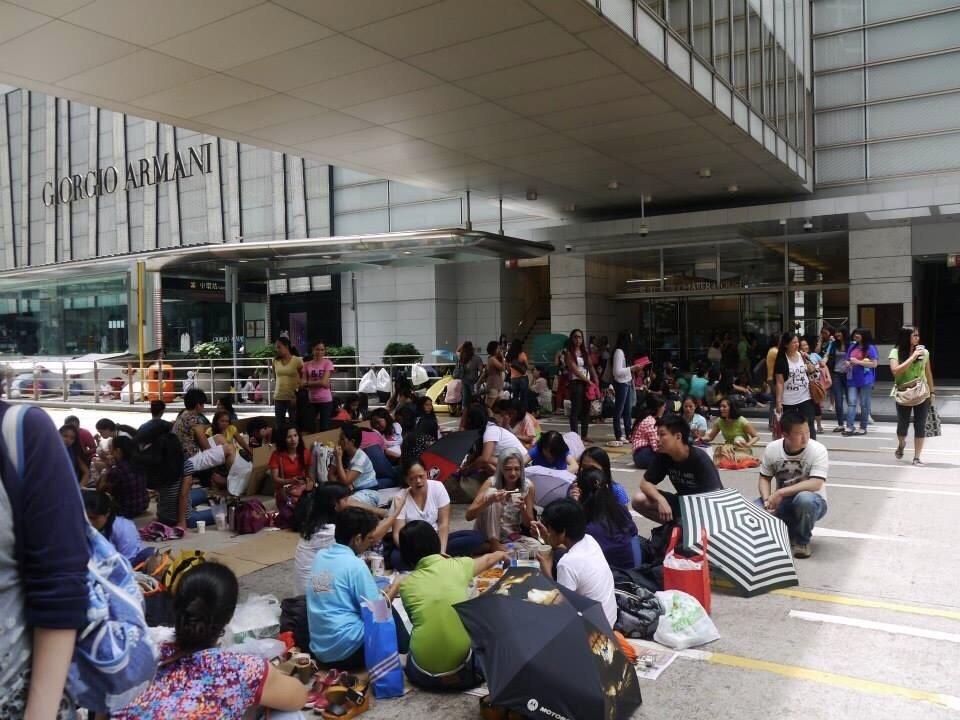 菲律賓移工坐在大廈角落陰涼處,她們在公共空間裡割出我群的狹小領域,或跟愛人枕肩軟語,或跟姐妹促膝為伴,相互為伴,在富泰又滄桑的港城裡活著。
