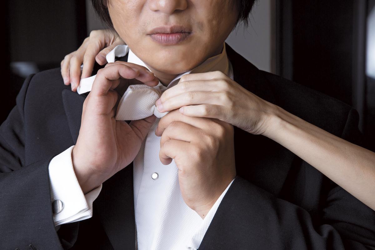 他形容為「天使」的太太,為他溫柔地繫上領結。