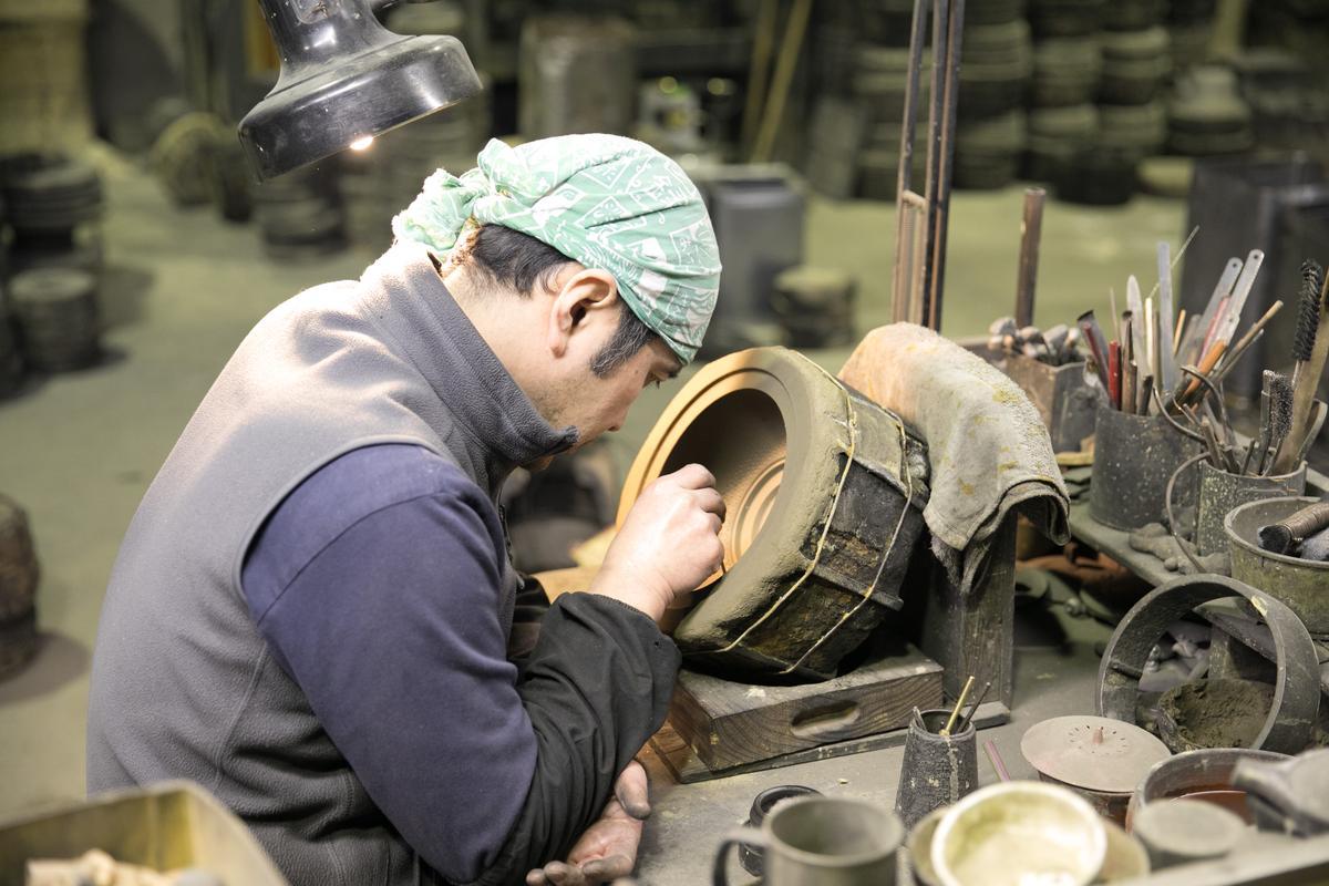 鑄鐵工匠單手托肘,專注地描繪花紋。