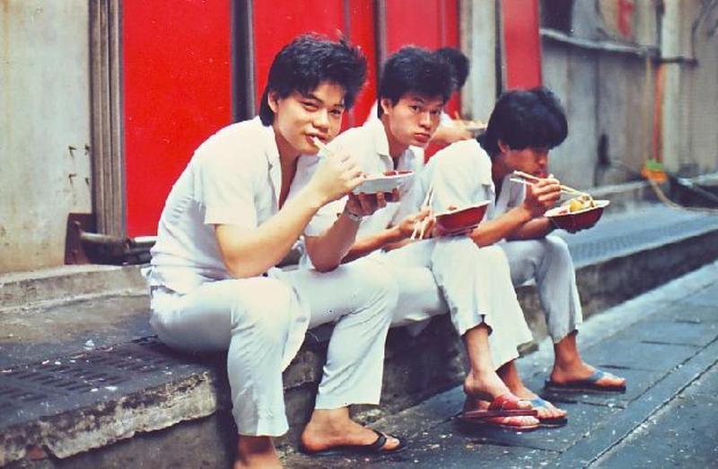 林志成(左1)18歲在蓮園餐廳當廚師,下班後與同事坐在路邊吃飯。(林志成提供)