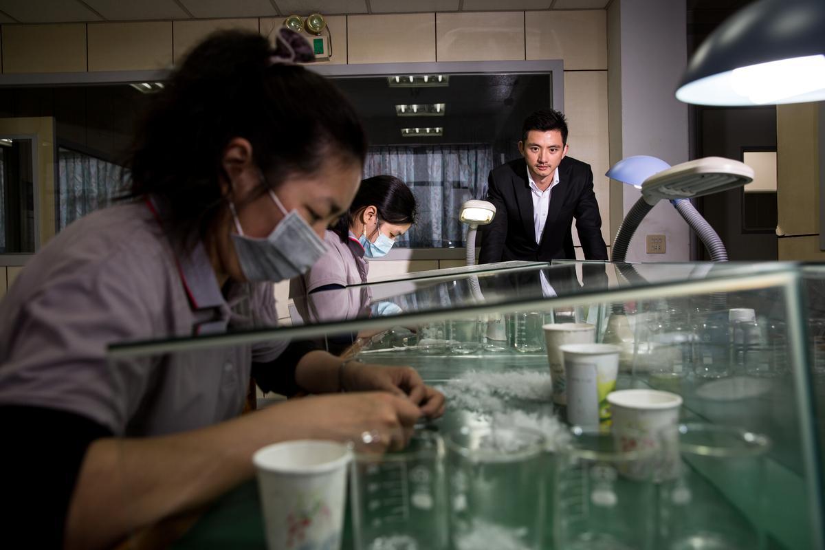 2008年,陳彥誠(右)陪父親陳焜耀度過安徽廠員工叛變,兩人開始一起跑馬拉松。圖為合隆大園廠員工正在挑揀羽絨雜質。