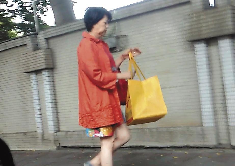 8月14日13:41,獅奶奶拎著超大水果提袋去取車,身上橘的紅的花的,衣著色彩繽紛。