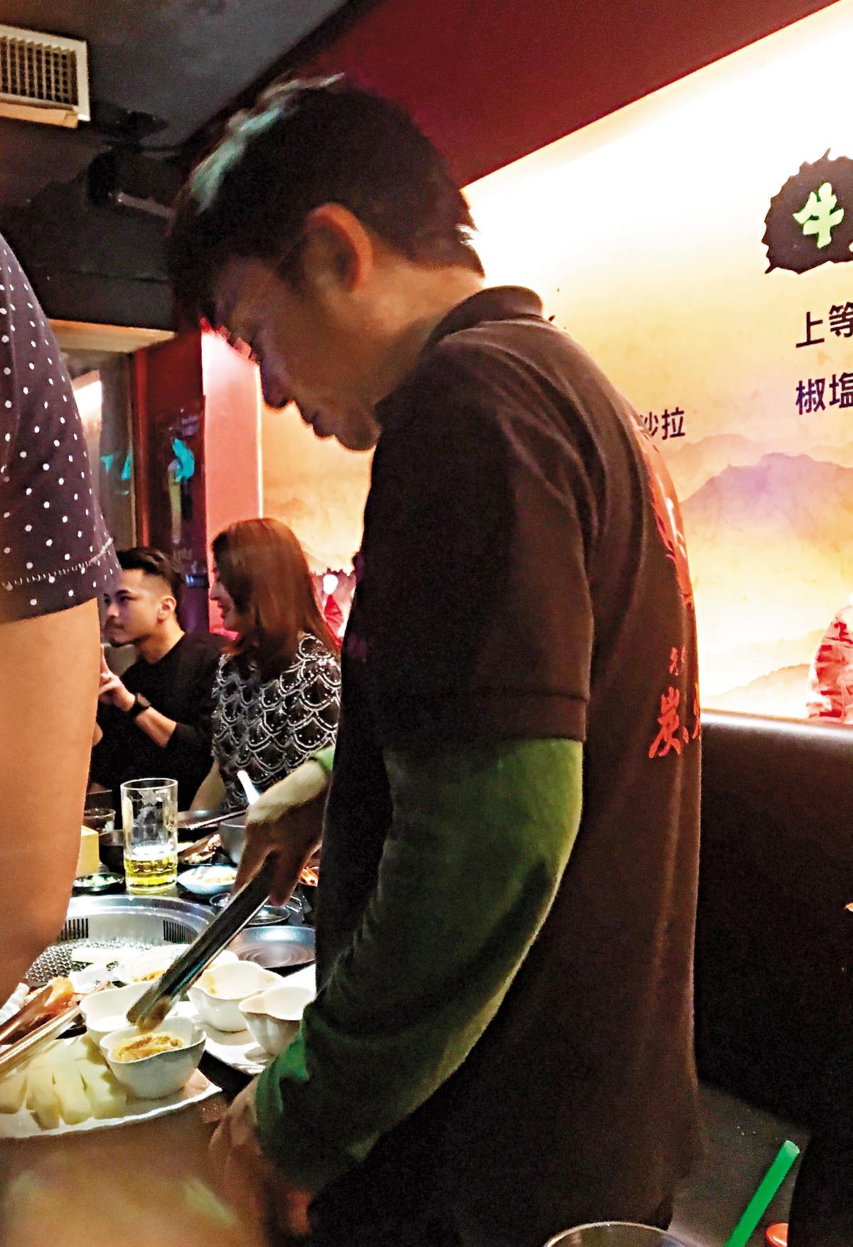 昔日民歌手江明學在燒肉店打工,為客人細心料理食材。(讀者提供)